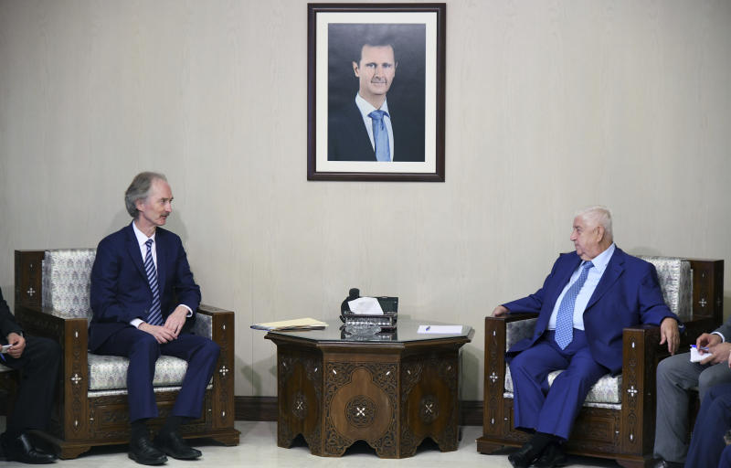 "In this photo released by the Syrian official news agency SANA, the U.N.'s special envoy for Syria Geir Pedersen, left, meets with Syrian Foreign Minister Walid al-Moallem, in Damascus, Syria, Monday, Sept. 23, 2019. Syria's state news agency SANA said Monday that al-Moallem discussed the formation of a constitutional committee and its work with Pedersen. SANA said al-Moallem's meeting with Pedersen on Monday focused on the committee's setup and guarantees that it be free ""from any foreign intervention."" (SANA via AP)"