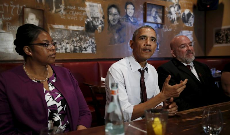 U.S. President Barack Obama speaks during his lunch meeting with formerly incarcerated individuals who have received commutations from his and previous administrations in Washington March 30, 2016. Flanking Obama are former inmates Romana Brant (L) and Phillip Emmert. REUTERS/Kevin Lamarque