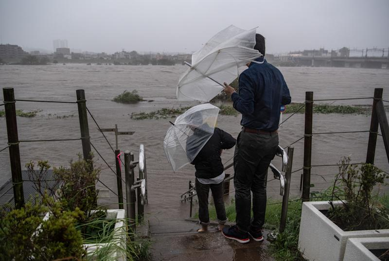 TOKYO, JAPAN - OCTOBER 12: People look at the flooded Tama River during Typhoon Hagibis on October 12, 2019 in Tokyo, Japan. Typhoon Hagibis is the most powerful typhoon to hit Japan this year and has been classed by the Japan Meteorological Agency as a 'violent typhoon' - the highest category on Japans typhoon scale. (Photo by Carl Court/Getty Images)