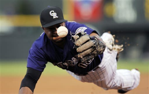 Colorado Rockies third baseman Chris Nelson knocks down a line drive by San Francisco Giants Marco Scutaro during the first inning of a baseball game in Denver on Monday, Sept. 10, 2012. (AP Photo/Chris Schneider)
