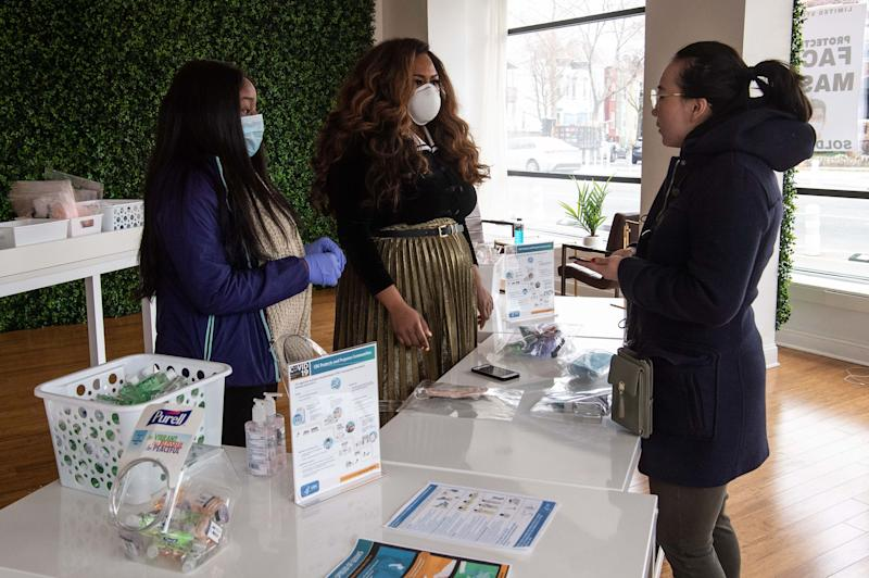 Adilisha Patrom (C) and her assistant (L) speak to a customer in her coronavirus pop-up store in Washington, DC, on March 6, 2020. - As supplies of face masks and hand sanitizer have dwindled due to the outbreak of Covid-19, Adilisha Patrom, owner of the Suites DC, a co-working and event space, who had bought a stock of face masks for her father who is suffering from cancer, decided to share her trove with the community. US lawmakers passed an emergency USD 8.3 billion spending bill to combat the coronavirus on Thursday as the number of cases surged in the country's northwest and deaths reached 12. Since then the toll has risen to 12 and the virus has spread to at least 15 states -- the latest being Maryland adjacent to the nation's capital Washington. (Photo by NICHOLAS KAMM / AFP) (Photo by NICHOLAS KAMM/AFP via Getty Images)