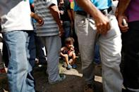 Emmanuel Cuauro, 4, seats on the sidewalk next to his mother Zulay Pulgar, as they make a line outside the hardware store to buy cement and re-sell it in Punto Fijo, Venezuela November 17, 2016. REUTERS/Carlos Garcia Rawlins