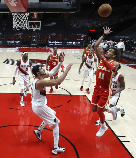 Atlanta Hawks guard Trae Young, right, shoots over Portland Trail Blazers center Enes Kanter during the first half of an NBA basketball game in Portland, Ore., Saturday, Jan. 16, 2021. (AP Photo/Craig Mitchelldyer)