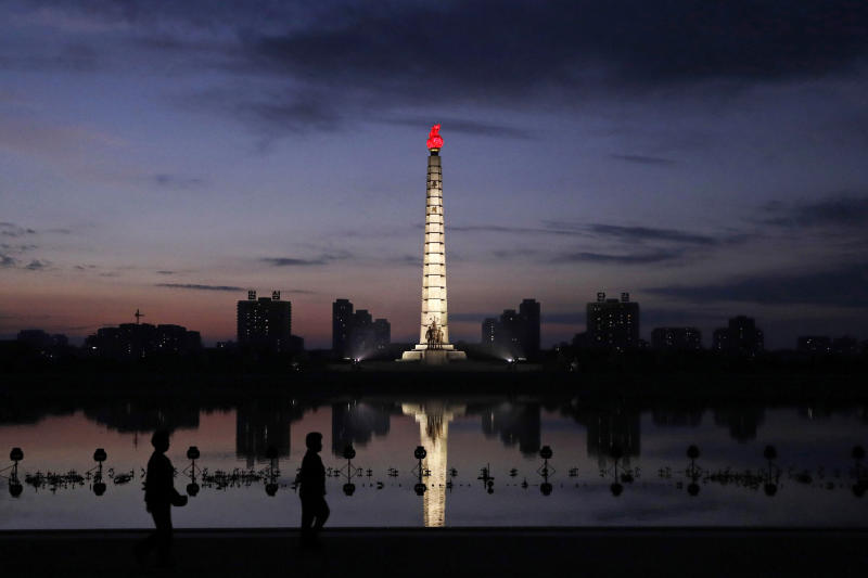 In this Sept. 15, 2018, photo, North Koreans take a walk at dawn by the Tower of Juche Idea in Pyongyang, North Korea. The word Juche is splashed across countless propaganda signs in North Korea and featured in hundreds of state media reports, and while it's technically a political ideology, it can seem more like a religion because of its difficulty for many outsiders to grasp and ability to inspire devotion among North Koreans. (AP Photo/Kin Cheung)