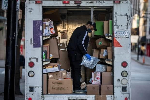 A FedEx employee sorts through multiple packages to be delivered in downtown Vancouver on Dec. 1, 2020. (Ben Nelms/CBC - image credit)