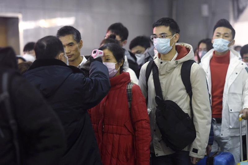 As the coronavirus outbreak goes global, a worker is seen here using an infrared thermometer to check temperatures of arriving train passengers.