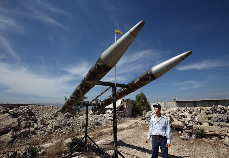 In this picture taken on Thursday May 23, 2013, a Lebanese man looks at Hezbollahs' mock rockets, at the Khiam prison which was used by Israeli troops during their occupation of southern Lebanon and which was destroyed in the 2006 war, at the southern Lebanese village of Khiam, Lebanon. While memories of Israel's rule and Hezbollah's defiance during two decades of south Lebanon occupation are still raw in the south, the Iran-backed group's strategic decision to send fighters to Qusair, a Syrian town near the Lebanese border, has raised concerns that Hezbollah will get sucked deep into the civil war next door, depleting its ability to defend Lebanon in a future confrontation with Israel. (AP Photo/Hussein Malla)