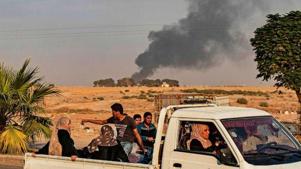 PHOTO: Civilians ride a pickup truck as smoke billows following Turkish bombardment in the northeastern town of Ras al-Ain in Syria's Hasakeh province along the Turkish border on Oct. 9, 2019. (Delil Souleiman/AFP via Getty Images)