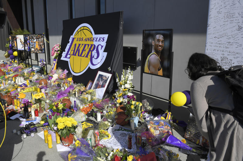 Fans look at a memorial to former Los Angeles Lakers player Kobe Bryant at the NBA basketball team's practice facility Wednesday, Jan. 29, 2020, in El Segundo, Calif. Bryant, his 13-year-old daughter, Gianna, and seven others died in a helicopter crash on Sunday, Jan. 26.  (AP Photo/Mark J. Terrill)