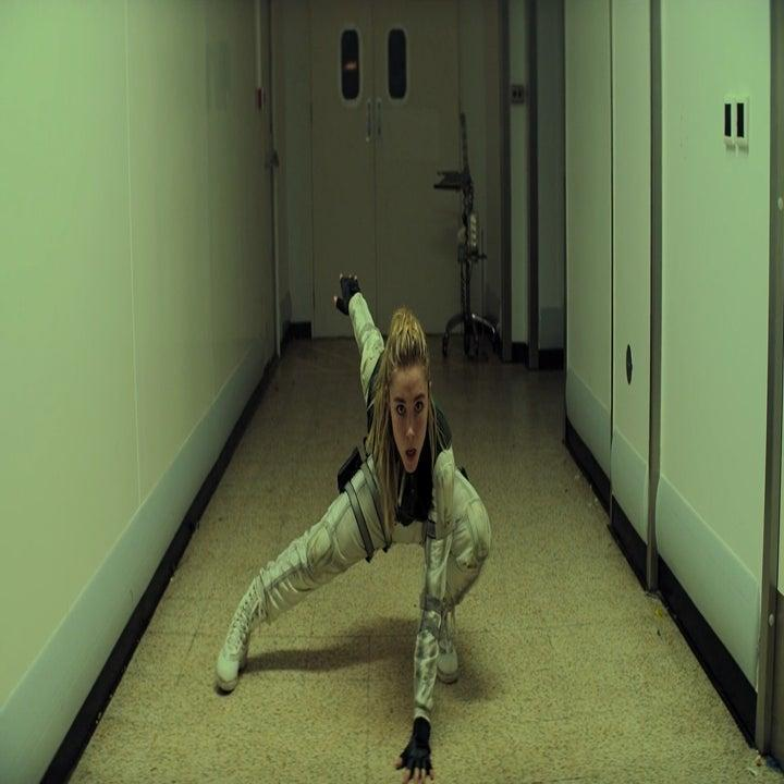 A woman crouching on the ground with her one foot stretched outward.