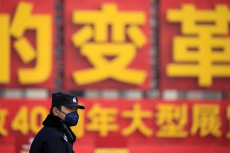 Police officer wearing a mask stands guard outside the Great Hall of the People ahead of the opening session of the Chinese People's Political Consultative Conference (CPPCC)