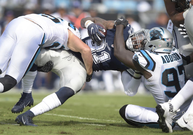 FILE - In this Sunday, Sept. 9, 2018, file photo, Dallas Cowboys' Ezekiel Elliott (21) is tackled by Carolina Panthers' Mario Addison (97) during the first half of an NFL football game in Charlotte, N.C. It's no secret that Dak Prescott and his revamped group of Dallas receivers hold the key to creating consistent running room for Elliott. The formula needs improvement with the Cowboys trying to avoid their first 0-2 start under Jason Garrett. (AP Photo/Mike McCarn, File)