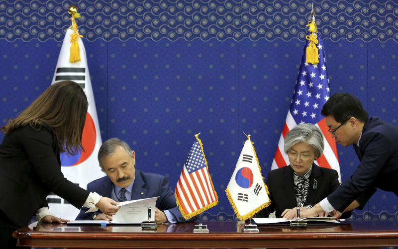 South Korean Foreign Minister Kang Kyung-wha, second from right, and U.S. Ambassador to South Korea Harry Harris, second from left, sign documents at Foreign Ministry in Seoul, South Korea, Friday, March 8, 2019. South Korea and the United States have formally signed a deal that increases Seoul's financial contribution for the deployment of U.S. troops in the Asian country. (AP Photo/Ahn Young-joon, Pool)