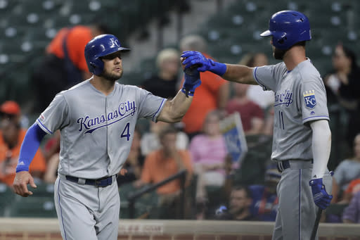 Kansas City Royals' Alex Gordon, left, is greeted near the dugout by Bubba Starling after scoring on a sacrifice fly by Meibrys Viloria during the second inning of the team's baseball game against the Baltimore Orioles, Tuesday, Aug. 20, 2019, in Baltimore. (AP Photo/Julio Cortez)