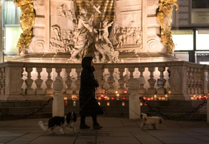 Woman and her dogs walk past candles left next to the plague column (Trinity Column) in Vienna's city center (AFP Photo/ALEX HALADA)