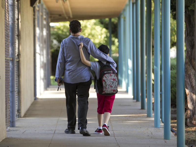 In this photo taken Monday, Aug. 13, 2012, Matthew Asner walks his son Will, 9, who is autistic, to the Nestle Avenue Elementary School in the Tarzana district of Los Angeles. Public school districts are seeing higher proportions of children with special needs due to declining enrollment and charter schools that do not accept as many kids with disabilities, especially more severe disabilities. This raises a question of equitable access for these kids, as well as cost issues for school districts. (AP Photo/Damian Dovarganes)