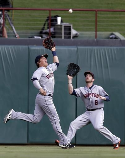 Houston Astros left fielder Enrique Hernandez reaches up to grab a fly out by Texas Rangers' Alex Rios in front of center fielder Alex Presley (8) in the first inning of a baseball game, Monday, July 7, 2014, in Arlington, Texas. (AP Photo/Tony Gutierrez)