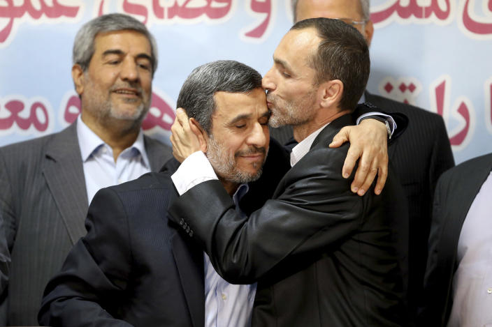 Hamid Baghaei, right, close ally of former Iranian President Mahmoud Ahmadinejad kisses his head after registering their candidacy for the upcoming presidential elections at the Interior Ministry in Tehran, Iran, Wednesday, April 12, 2017. Ahmadinejad on Wednesday unexpectedly filed to run in the country's May presidential election, contradicting a recommendation from the supreme leader to stay out of the race. Other close ally of Ahmadinejad, Esfandiar Rahim Mashie accompanies them. (AP Photo/Ebrahim Noroozi)