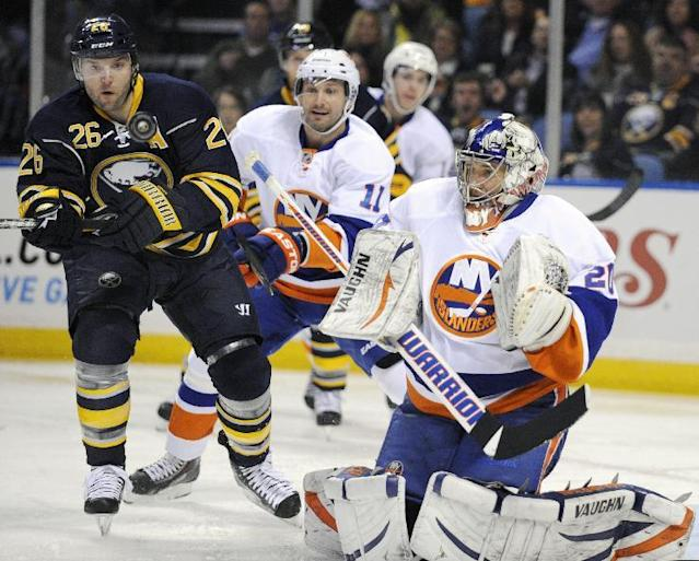 File - This Feb. 23, 2013 file photo shows Buffalo Sabres' left winger Thomas Vanek (26), of Austria, eyeing the puck with New York Islanders' defenseman Lubomir Visnovsky, (11) of the Czech Republic, and goaltender Evgeni Nabokov (20), of Russia, during the first period of an NHL hockey game in Buffalo, N.Y. The New York Islanders announced Sunday Oct. 27, 2013, that they have acquired Vanek from the Buffalo Sabres in exchange for Matt Moulson, a first round selection in the 2014 NHL draft and a second round selection in 2015. (AP Photo/Gary Wiepert, File)
