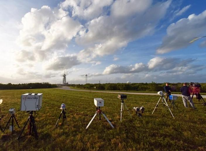 Remote cameras line a field near Pad 39A at Kennedy Space Center where the SpaceX Crew Dragon sits atop a Falcon 9 booster rocket