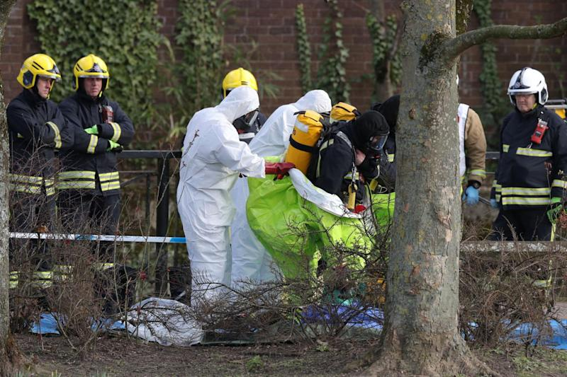 Personnel are helped out of their hazmat suits (Andrew Matthews/PA)