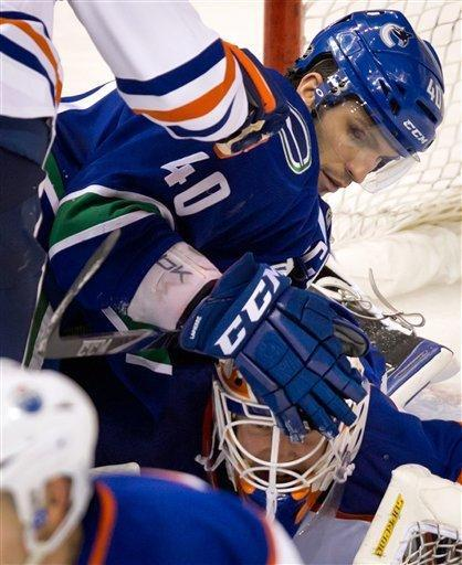 Vancouver Canucks' Maxim Lapierre, top, lands on Edmonton Oilers goalie Devan Dubnyk after being checked by Ryan Whitney, not pictured, during the second period of an NHL hockey game in Vancouver, British Columbia, on Tuesday, Jan. 24, 2012. (AP Photo/The Canadian Press, Darryl Dyck)