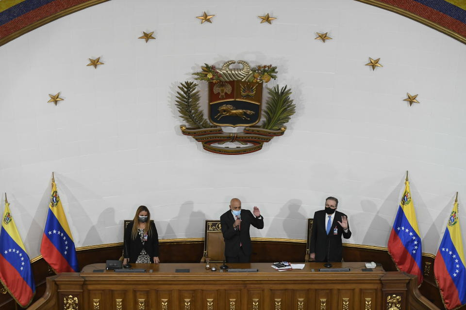 Jorge Rodriguez holds his hand up to swear-in lawmakers after he was sworn-in as president of the National Assembly in Caracas, Venezuela, Tuesday, Jan. 5, 2021, next to First Vice President of Congress Iris Varela, left, and Second Vice President Didalco Bolivar. The ruling socialist party assumed the leadership of Venezuela's congress, the last institution in the country it didn't already control. (AP Photo/Matias Delacroix)