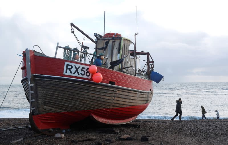 People walk past a fishing boat on the beach in Hastings