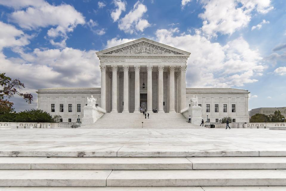 Taken at a moment when only a handful of people were in the scene, this straight-on image of the US Supreme Court shows the majesty of the structure. Home to the most powerful lawmakers in the country, this iconic building is centered under a blue sky with some scattered clouds.
