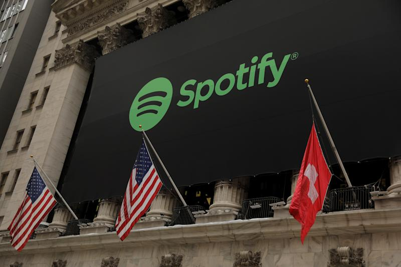 The Spotify logo hangs on the facade of the New York Stock Exchange with U.S. and a Swiss flag as the company lists it's stock with a direct listing in New York, U.S., April 3, 2018. REUTERS/Lucas Jackson