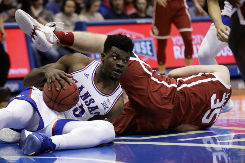 Kansas center Udoka Azubuike, left, comes up with the ball after a dive on the floor with Oklahoma forward Brady Manek, right, during the first half of an NCAA college basketball game in Lawrence, Kan., Saturday, Feb. 15, 2020. (AP Photo/Orlin Wagner)