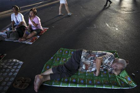 An anti-government protester sleeps on a road as others listen to a speech at the main intersection which protesters are occupying in downtown Bangkok February11, 2014. REUTERS/Damir Sagolj