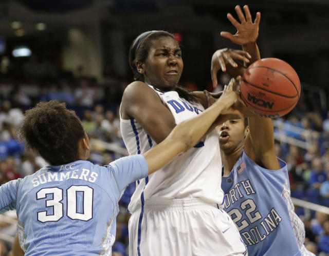 Duke's Elizabeth Williams, center, is fouled as she tries to shoot between North Carolina's Hillary Summers, left, and N'Dea Bryant, right, during the first half of an NCAA college basketball semi-final game at the Atlantic Coast Conference tournament in Greensboro, N.C., Saturday, March 8, 2014. (AP Photo/Chuck Burton)