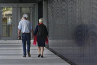 Two people hold hands as they walk to the court where relatives were to give testimony in the trial of four men charged with murder over the downing of Malaysia Airlines flight MH17, at Schiphol airport, near Amsterdam, Netherlands, Monday Sept. 6, 2021. Relatives of some of the 298 people killed in the downing of Malaysia Airlines flight MH17 tell a Dutch court about the impact on their lives of the disaster during the trial of three Russians and a Ukrainian charged with involvement in bringing down the Amsterdam-Kuala Lumpur flight more than seven years ago. (AP Photo/Peter Dejong)