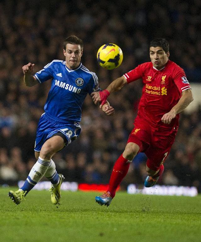 Chelsea's Cesar Azpilicueta, left, fights for the ball with Liverpool's Luis Suarez, during their English Premier League soccer match, at the Stamford Bridge Stadium in London, Sunday, Dec. 29, 2013. (AP Photo/Bogdan Maran)