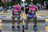 "FILE - In this June 24, 2020, file photo, Tyshawn, 9, left, and his brother Tyler, 11, right, of Baltimore, hold signs saying ""Black Lives Matter"" and ""I Can't Breathe"" as they sit on a concrete barrier near a police line as demonstrators protest along a section of 16th Street that has been renamed Black Lives Matter Plaza in Washington. Thousands of Black activists from across the U.S. will hold the 2020 Black National Convention on Aug. 28, 2020, via livestream to produce a new political agenda that builds on the protests that followed George Floyd's death. Organizers of the gathering shared their plans with The Associated Press on Wednesday, July 1, ahead of an official announcement. (AP Photo/Jacquelyn Martin, File)"