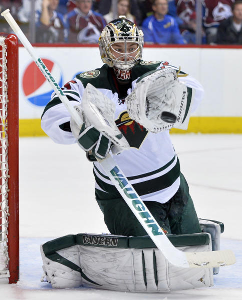Minnesota Wild goalie Darcy Kuemper (35) blocks a shot by the Colorado Avalanche in the second period of Game 2 of an NHL hockey first-round playoff series on Saturday, April 19, 2014, in Denver. (AP Photo/Jack Dempsey)