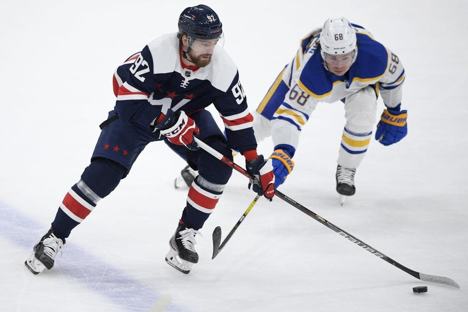 Washington Capitals center Evgeny Kuznetsov (92) skates with the puck against Buffalo Sabres left wing Victor Olofsson (68) during the second period of an NHL hockey game Thursday, April 15, 2021, in Washington. (AP Photo/Nick Wass)