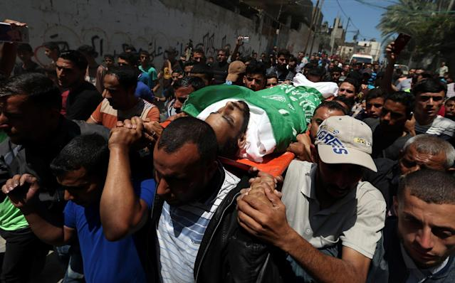 <p>Mourners carry the body of a Palestinian, who was killed during a protest against U.S embassy move to Jerusalem at the Israel-Gaza border, during his funeral in the central Gaza Strip, May 15, 2018. (Photo: Ibraheem Abu Mustafa/Reuters) </p>