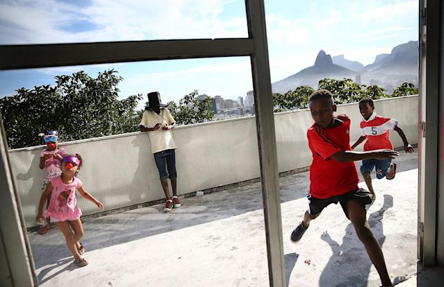 RIO DE JANEIRO, BRAZIL - FEBRUARY 22: Young revelers celebrate during pre-Carnival festivities in the Cantagalo shantytown community next to neighboring Pavao-Pavaozinho on February 22, 2014 in Rio de Janeiro, Brazil. The pacified favelas stand above Copacabana and Ipanema beaches. Ahead of the World Cup, some of Rio's pacified favelas have seen an increase in violence, including a number of shootings in Cantagalo and Pavao-Pavaozinho. Around 10,000 people live in the Cantagalo and Pavao-Pavaozinho communities with a total of 1.7 million Rio residents residing in shantytowns, many of which are controlled by drug traffickers. on February 22, 2014 in Rio de Janeiro, Brazil. (Photo by Mario Tama/Getty Images,)