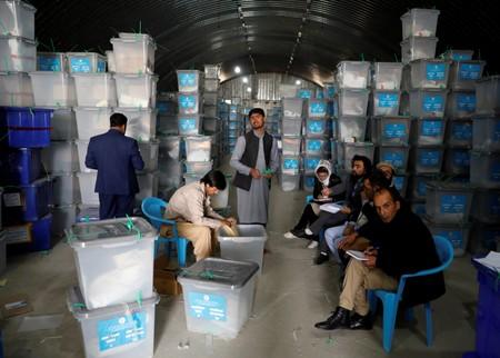 Afghan election commission worker opens ballot boxes and election materials at a warehouse in Kabul