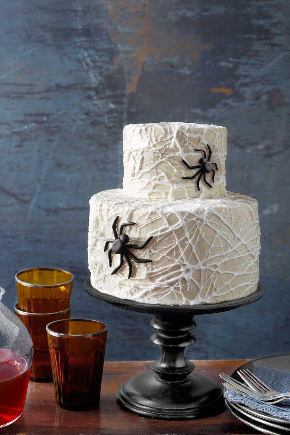 """<p>Weave a tangled web—from melted marshmallows—for this elegantly eerie dessert.</p><p><strong>Step 1: </strong>Prepare two boxes of cake mix (any flavor) per the package instructions. You'll need two round cake pans: one 4""""W x 4""""H; the other 7""""W x 4""""H.</p><p><em><em><em><em>Trace the base of one pan onto parchment; cut out and place in the bottom of that pan. Repeat for the other pan. Coat the inside of both pans, including parchment liners, with cooking spray.</em></em></em><br></em></p><p><strong><strong>Step 2:</strong> </strong>Apportion cake batter between pans. In a 350°F oven, bake the smaller cake for 25 to 30 minutes and the larger cake for 45 to 50 minutes. Let cool.</p><p><strong>Step 3:</strong> Level the top of each cake. Frost the top of the larger cake with white buttercream. Then center the smaller cake atop it. Frost the entire two-tiered cake.</p><p><strong>Step 4:</strong> Microwave eight ounces of marshmallows in a bowl for 30 seconds, until gooey but still lumpy. Stir until smooth and cool enough to handle. Pinch off a bit of marshmallow; stretch to create a long, thin strand; and drape it onto the cake. Repeat, applying strands until the entire cake is covered in """"webbing.""""</p><p><strong>Step 5:</strong> To make the spiders, you'll need black fondant. Use your hands to shape one 1½-inch ball and nine ½-inch ones. Partially flatten the tops of the large ball and one small one; then use a drop of water to attach them, creating the head and body. Roll the remaining balls into long tubes for the legs, bend in the middle, and attach, using a drop of water for each, to the body, as shown. Repeat, using slightly smaller balls, to create a second spider. </p><p><strong><a href=""""https://www.countryliving.com/food-drinks/recipes/a1568/circus-tent-frosting-3678/"""" rel=""""nofollow noopener"""" target=""""_blank"""" data-ylk=""""slk:Get recipe for buttercream"""" class=""""link rapid-noclick-resp"""">Get recipe for buttercream</a>.</strong></p>"""