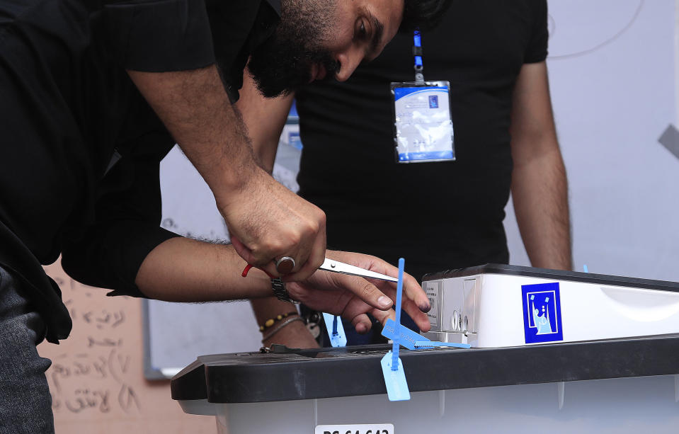 An election worker opens a ballot box after the polls closed in Baghdad, Iraq, Sunday, Oct. 10, 2021. Polls have closed across Iraq Sunday evening in parliamentary elections that were held months ahead of schedule in response to a popular uprising against corruption and mismanagement. (AP Photo/Hadi Mizban)