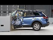 """<p>Time has been better to the Mazda CX-9 than others. Today's Mazda CX-9 has multiple 10Best awards, and, more recently, a Top Safety Pick+ award from the IIHS. Things were not always this way. A Poor rating was given to the first-gen CX-9 during driver-side small overlap crash testing. During the test, the dummy barely made contact with the airbag, and ended up hitting the window frame as the steering column and its airbag continued to move up and away from the dummy as the collision occurred. The CX-9's side airbag never deployed, and the dummy's legs looked pinched between the seat and the lower dashboard after the crash. The same CX-9 scored better during the moderate overlap front and side crash tests, getting Good ratings in both. Today every vehicle in Mazda's lineup—except for the MX-5 Miata, which hasn't been tested—has earned a Top Safety Pick+ rating from the IIHS. </p><p><a href=""""https://www.youtube.com/watch?v=2qXOiri3vTU"""" rel=""""nofollow noopener"""" target=""""_blank"""" data-ylk=""""slk:See the original post on Youtube"""" class=""""link rapid-noclick-resp"""">See the original post on Youtube</a></p>"""
