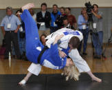 2010 world champion Kayla Harrison (L) is thrown onto the mat by 2008 Olympian Travis Stevens (R) during a judo demonstration at the U.S. Olympic Committee Media Summit in Dallas, Texas May 13, 2012. REUTERS/Tim Sharp