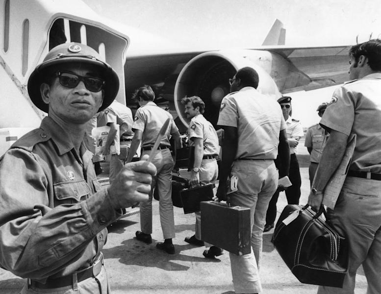 In this March 28, 1973 photo, a Viet Cong observer of the Four Party Joint Military Commission counts U.S. troops as they prepare to board jet aircraft at Saigonís Tan Son Nhut airport. As the last U.S. combat troops left Vietnam 40 years ago, angry protesters still awaited them at home. North Vietnamese soldiers took heart from their foes' departure, and South Vietnamese who had helped the Americans feared for the future. While the fall of Saigon two years later — with its indelible images of frantic helicopter evacuations — is remembered as the final day of the Vietnam War, Friday marks an anniversary that holds greater meaning for many who fought, protested or otherwise lived it.  (AP Photo/Neal Ulevich)