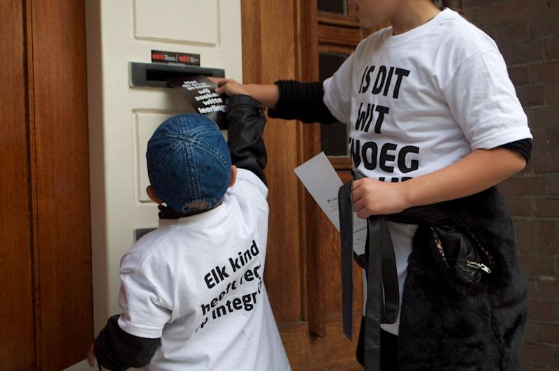 Marching door to door in Amsterdam, the children chant: 'Don't think black, don't think white, don't think black and white: think the colours of your heart.' (AFP Photo/Charlotte van Ouwekerke)