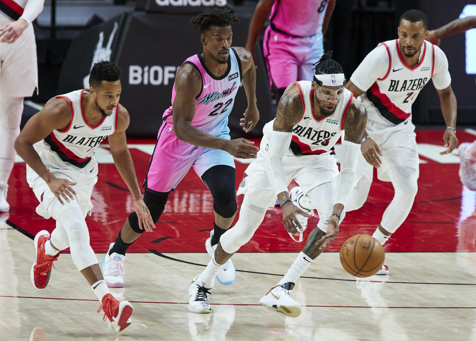 Portland Trail Blazers forward Robert Covington, second from right, leads a fast break with guard CJ McCollum, left, and forward Norman Powell, right, as Miami Heat forward Jimmy Butler trails behind during the second half of an NBA basketball game in Portland, Ore., Sunday, April 11, 2021. (AP Photo/Craig Mitchelldyer)