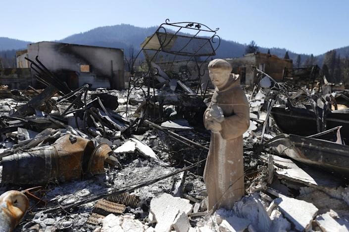 A religious statue stands amid rubble