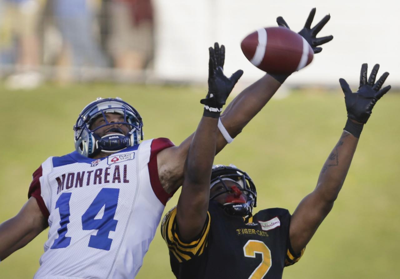 Montreal Alouettes' Brandon London (L) competes for the ball with Hamilton Tiger-Cats' Evan McCollough during the first half of the 2013 CFL Touchdown Atlantic game in Moncton, New Brunchwick, September 21, 2013. REUTERS/Devaan Ingraham (CANADA - Tags: SPORT FOOTBALL)